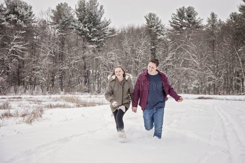 跑在雪的愉快的夫妇 免版税库存照片
