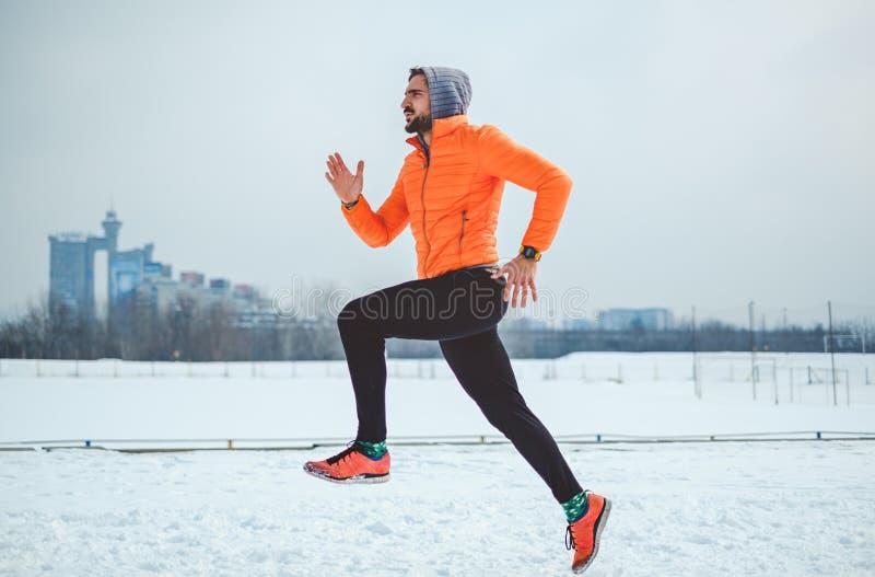 跑在雪的被聚焦的运动员 库存照片
