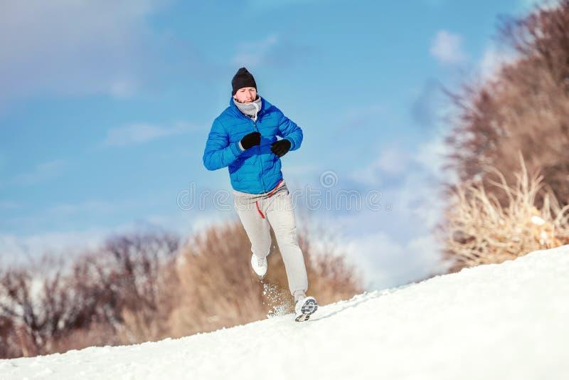跑在雪的运动员,为坚硬训练和锻炼做准备 库存图片