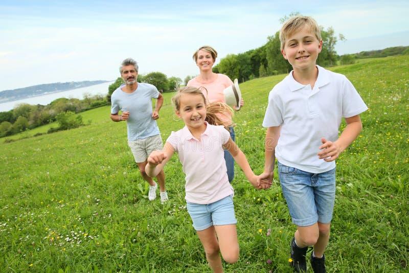 跑在领域的家庭 免版税库存图片