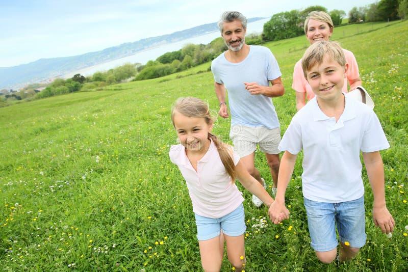 跑在领域的快乐的家庭 免版税库存图片