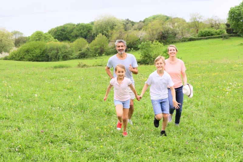 跑在领域的愉快的家庭 库存照片