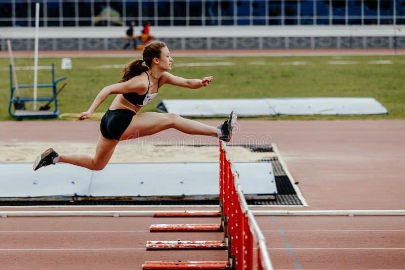 跑在100个米障碍的女子运动员 免版税库存图片