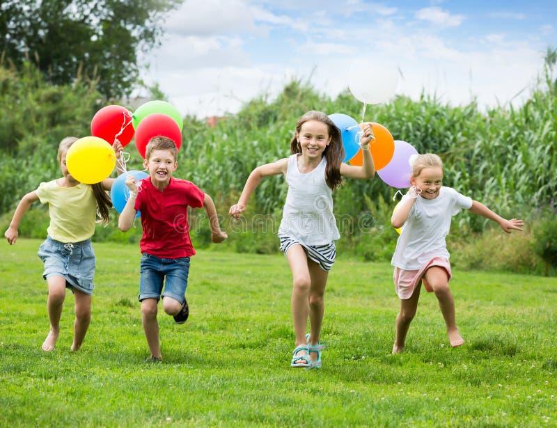 跑在绿色草坪的四个微笑的孩子 图库摄影