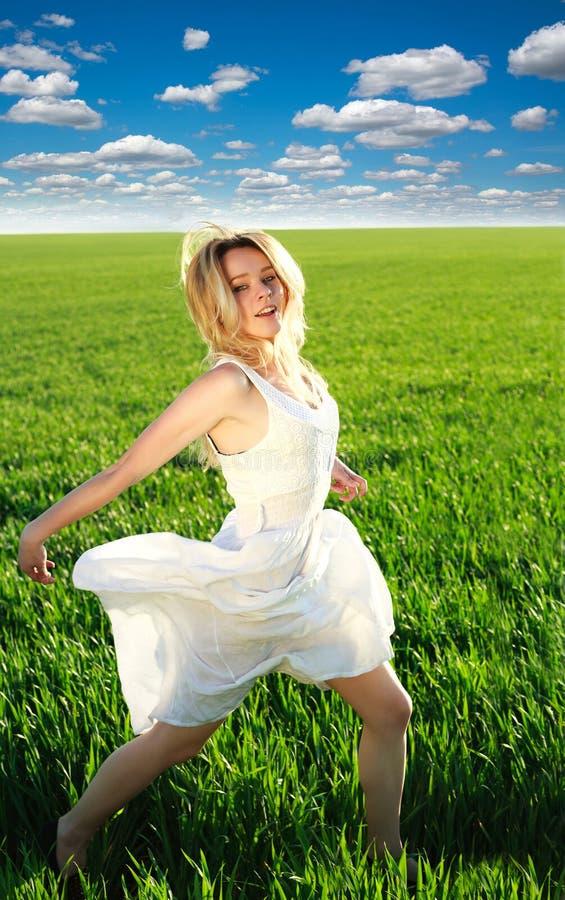 跑在绿色进展的领域的愉快的女孩在蓝天下 免版税库存照片