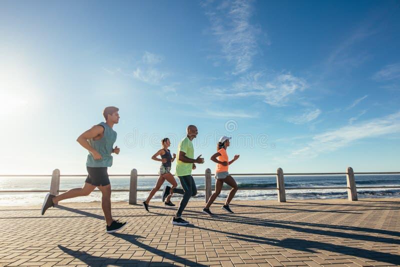 跑在洋锋的小组运动员 免版税库存照片