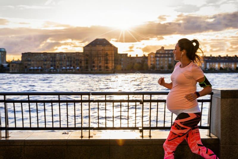 跑外面在城市的孕妇在河沿 免版税库存图片