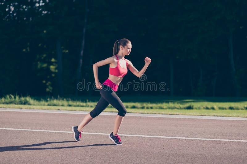 跑小姐的教练员户外,训练为马拉松奔跑 免版税库存图片
