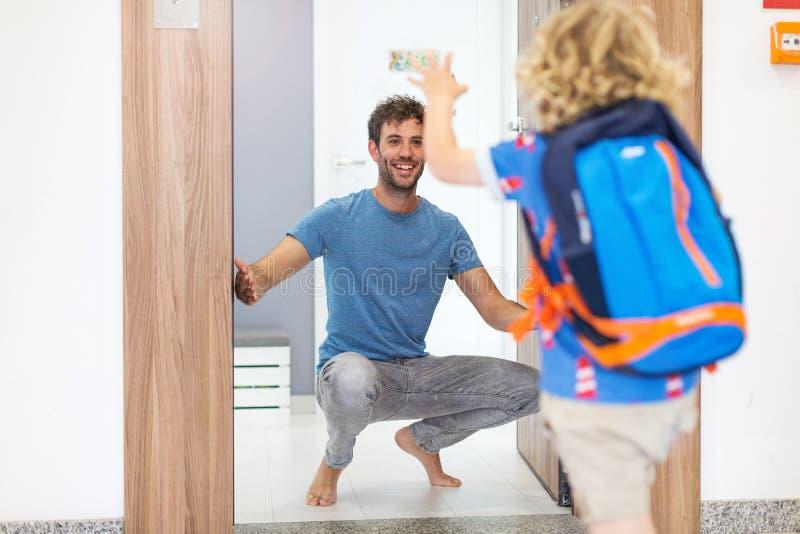 跑往他的父亲的小男孩在家等待他 免版税库存照片