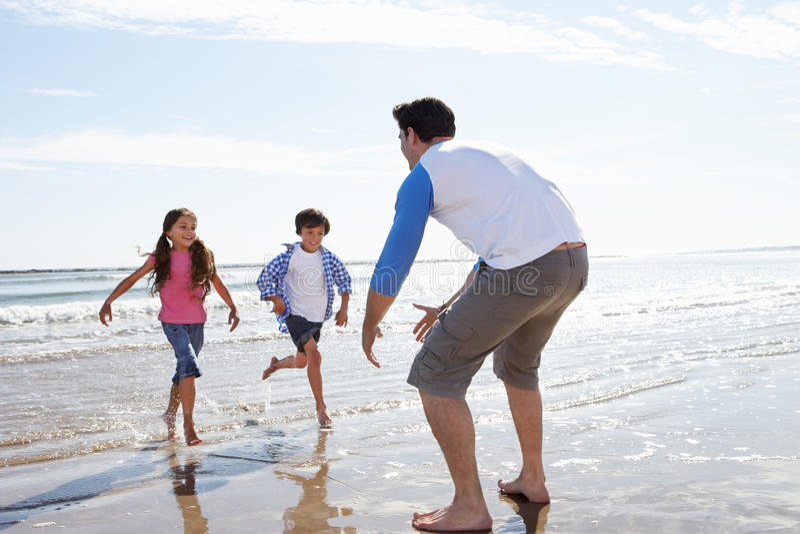 跑往海滩的父亲的孩子 库存图片