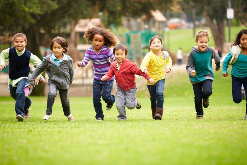 跑往照相机的小组幼儿在公园 库存照片