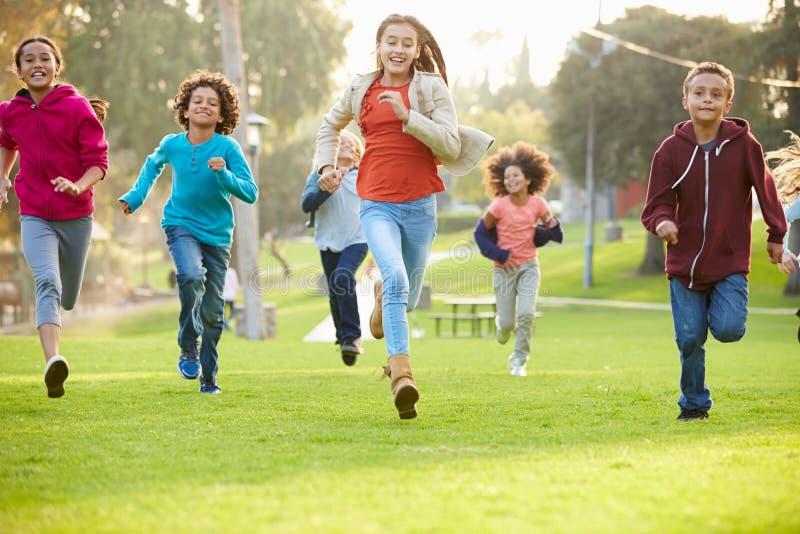 跑往照相机的小组幼儿在公园 免版税库存图片