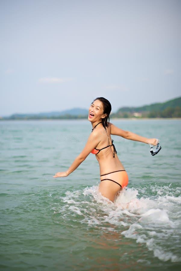 跑往水的亚裔女孩 免版税库存图片