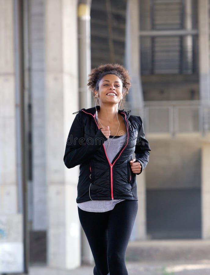 跑微笑的年轻的黑人妇女户外 免版税图库摄影