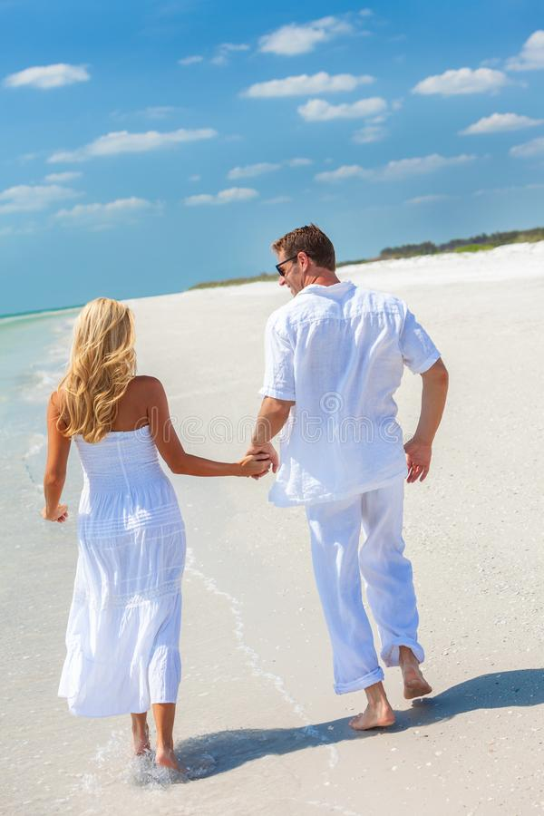 跑愉快的年轻的夫妇握在一个热带海滩的手 免版税库存图片