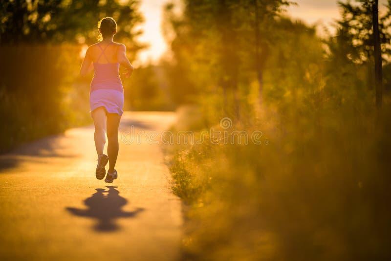 跑户外在一个可爱的晴朗的夏天evenis的年轻女人 免版税库存图片