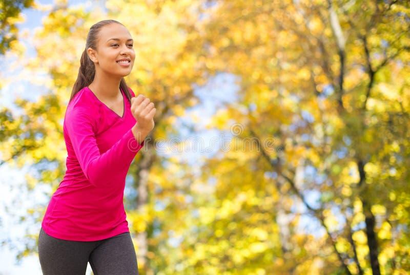 跑户外在秋天的微笑的妇女 免版税库存图片
