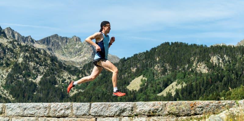 跑横跨在山的一个石墙的男性运动员 免版税库存图片