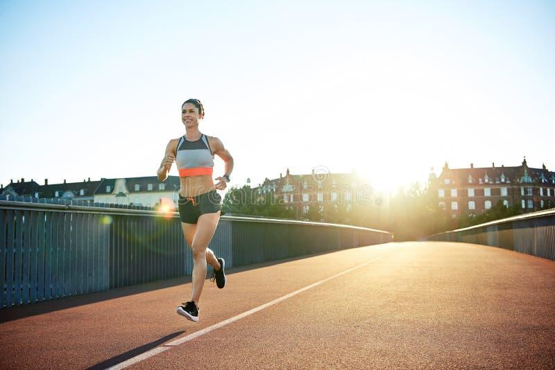 跑横跨桥梁的适合的运动少妇 库存图片