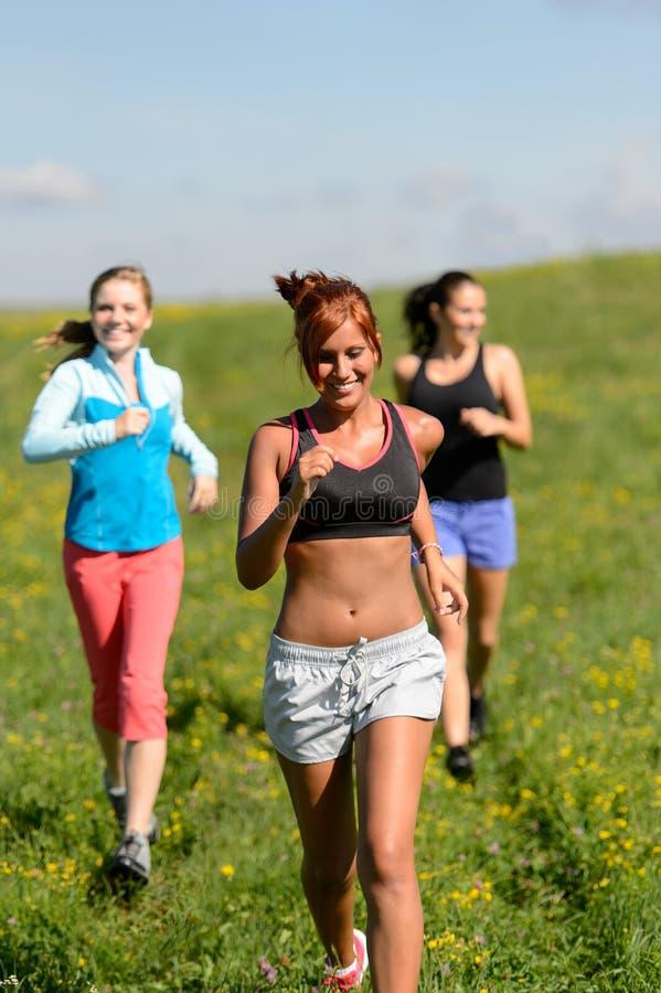 跑步下坡夏天草甸的三个女孩 库存照片