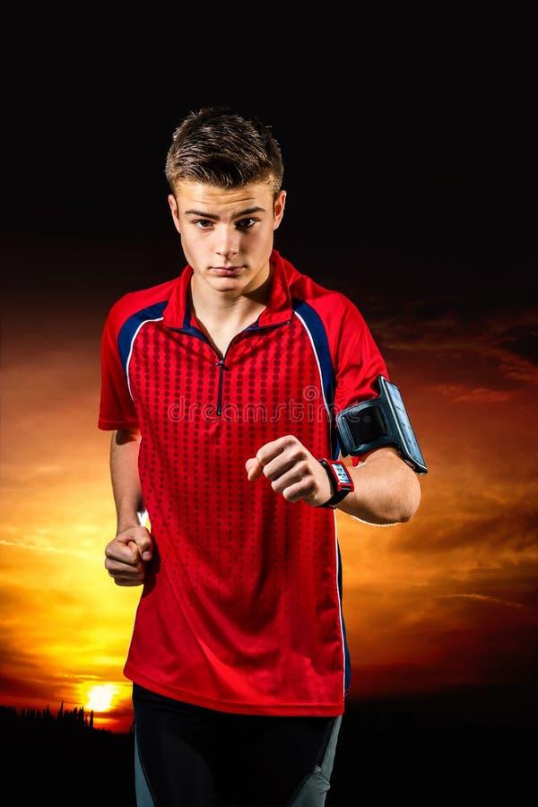 跑步与巧妙的手表的青少年的男孩在日落 免版税库存照片