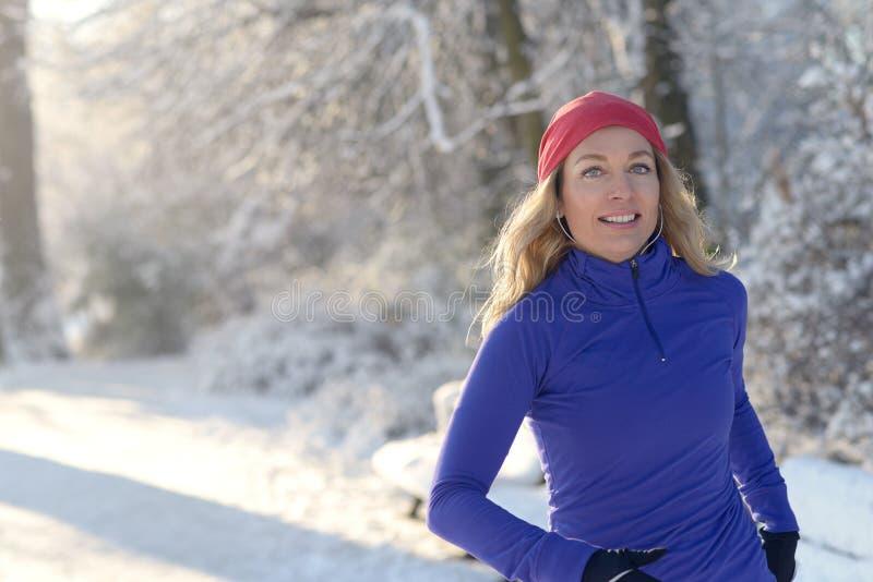 跑步在与耳机的冬天的俏丽的妇女 免版税库存照片