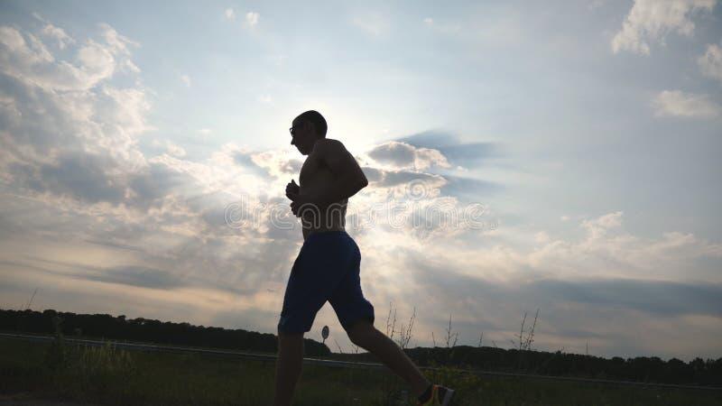 跑步在乡下公路的肌肉人剪影在日落 马拉松跑的室外的男性慢跑者训练 运动员 免版税库存照片