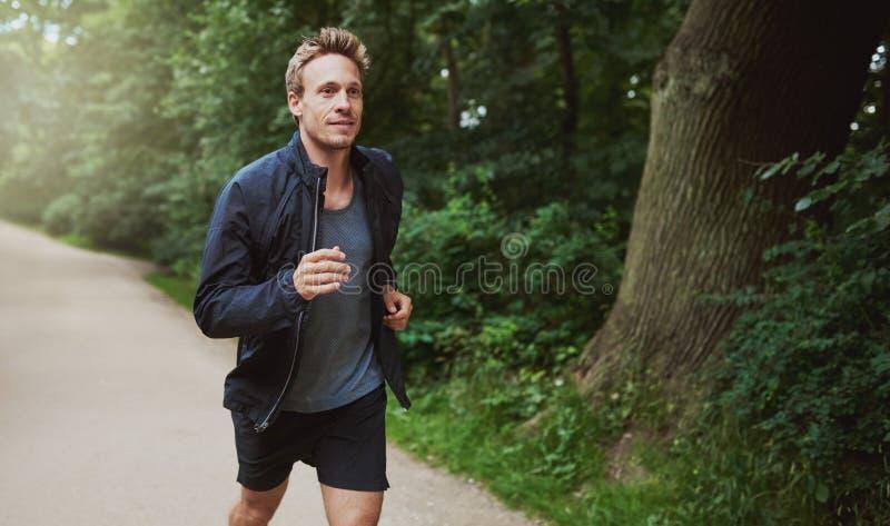 跑步在公园的夹克的健康人 免版税库存照片