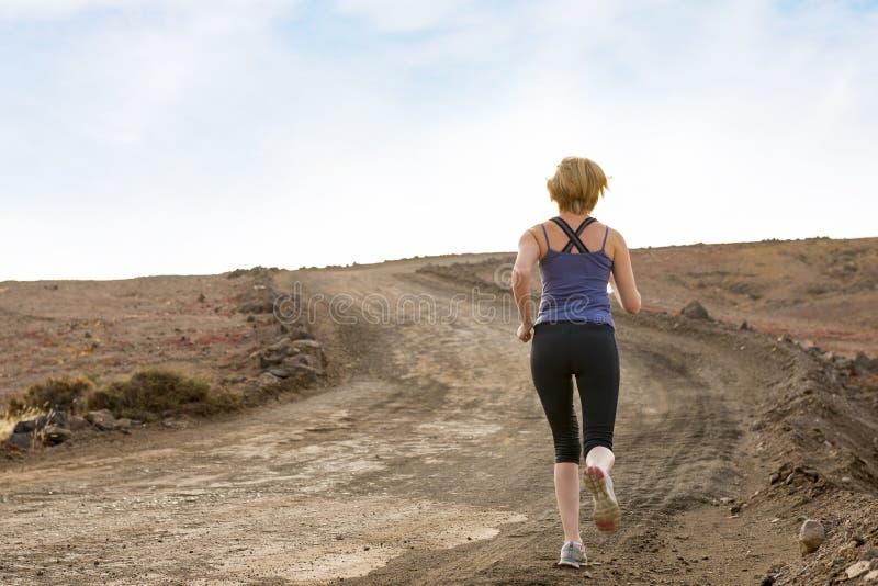 跑步在土足迹的妇女 库存照片