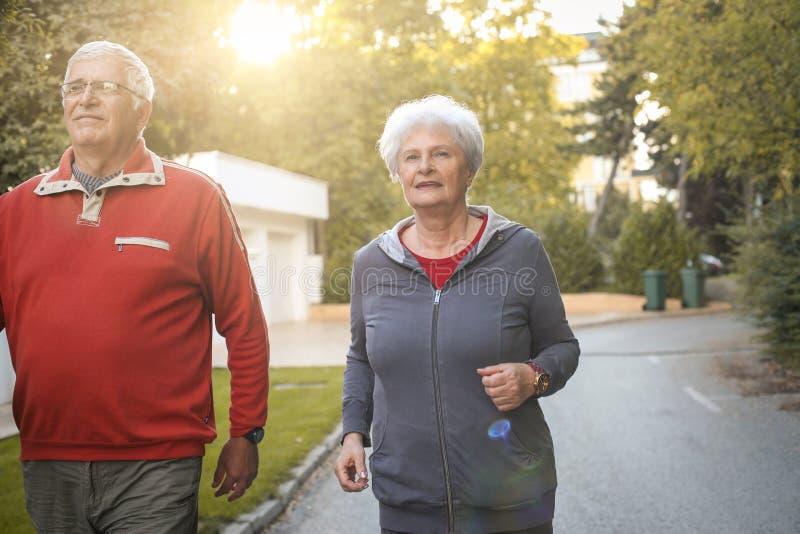 跑步在城市公园的微笑的资深夫妇 免版税图库摄影