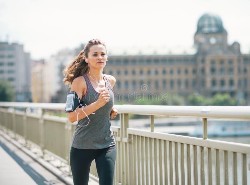 跑步在城市的健身少妇 免版税库存照片