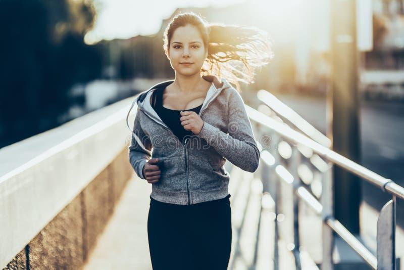 跑步在城市的运动的妇女 免版税库存照片