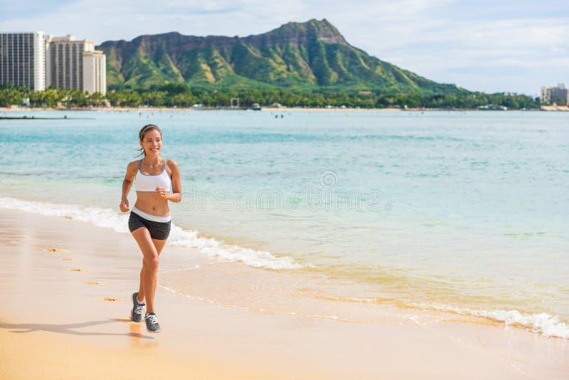 跑步在威基基,檀香山,奥阿胡岛,夏威夷,美国的夏威夷海滩奔跑亚洲妇女体育连续健身 女孩运动员赛跑者训练 库存图片