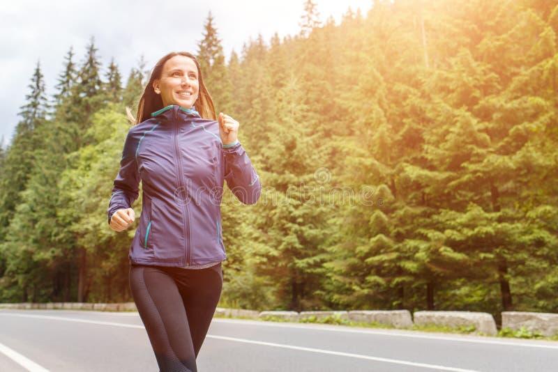 跑步在山路的年轻微笑的妇女 免版税库存照片