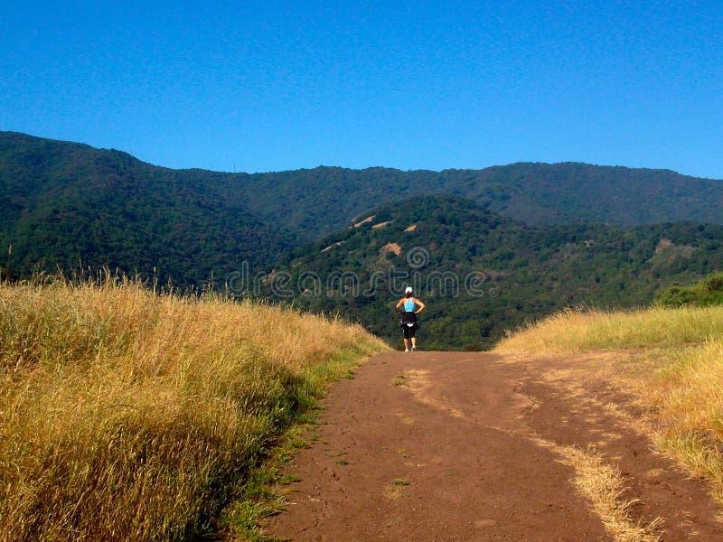 跑步在山道路的活跃妇女 免版税库存图片
