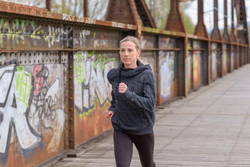 跑步在桥梁的苗条运动妇女 免版税库存照片