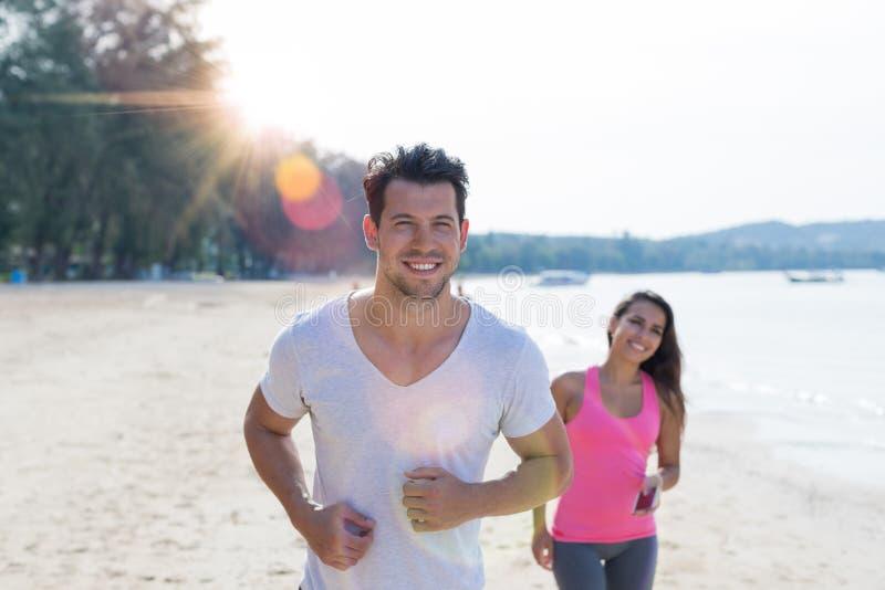 跑步在海滩的夫妇连续男人和妇女体育赛跑者制定出微笑的愉快的适合男性和女性健身慢跑者 免版税图库摄影