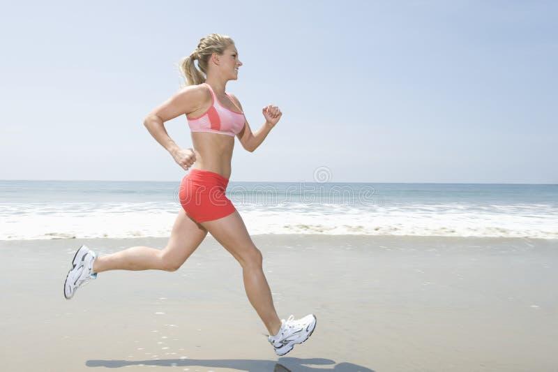 跑步在海滩的妇女 免版税库存图片