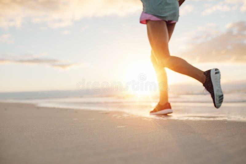 跑步在海滩的少妇的脚 免版税图库摄影