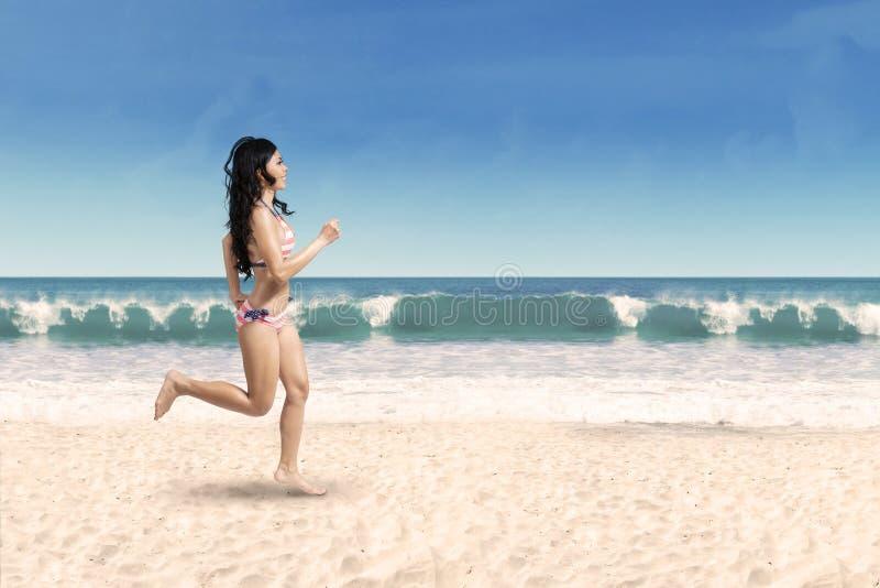 跑步在海滩的愉快的妇女 免版税图库摄影