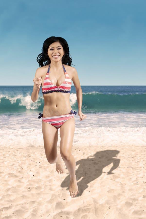 跑步在海滩的比基尼泳装的快乐的妇女 图库摄影