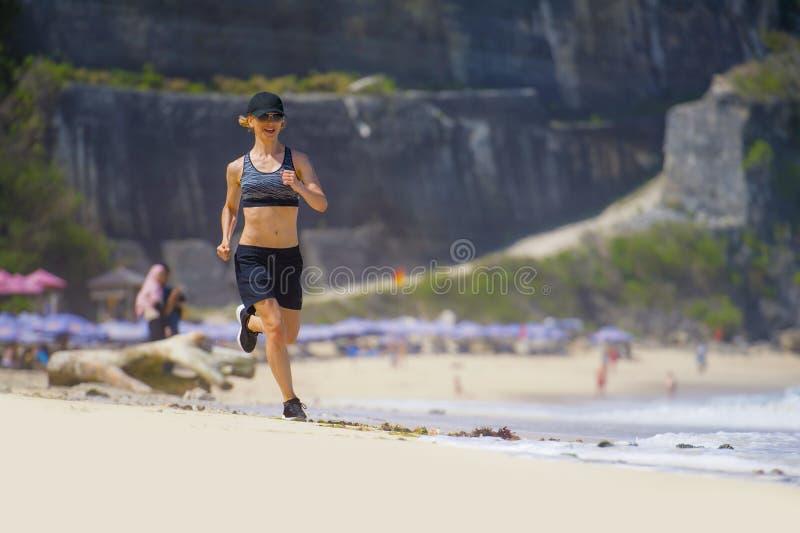 跑步在热带天堂海滩陈列适合和运动身体的连续锻炼的年轻愉快和可爱的体育赛跑者妇女 库存图片