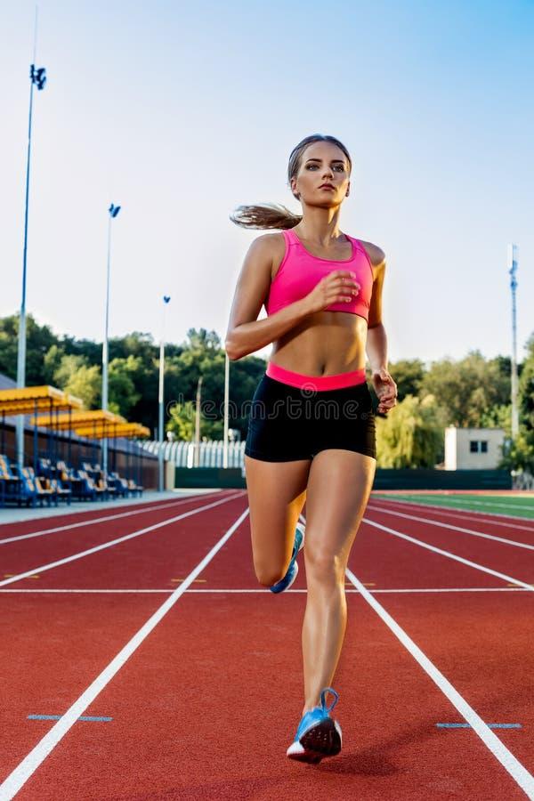 跑步在红色连续轨道的运动的健身妇女在体育场内 户外训练夏天在与绿色的连续轨道线 免版税库存照片