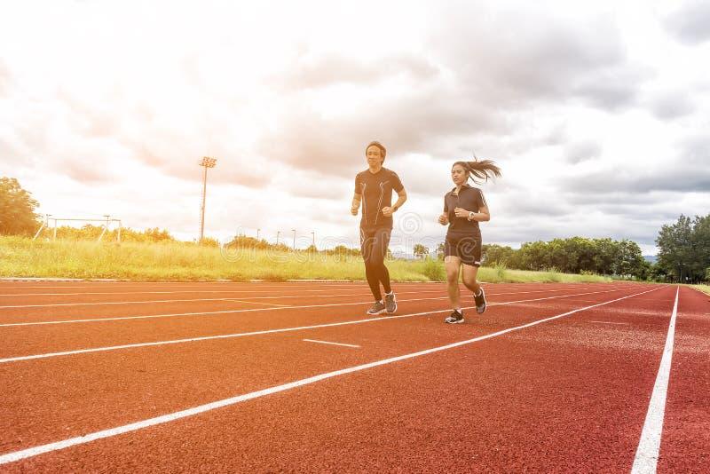 跑步在赛马跑道、体育和社交活动概念的两个赛跑者 免版税库存图片