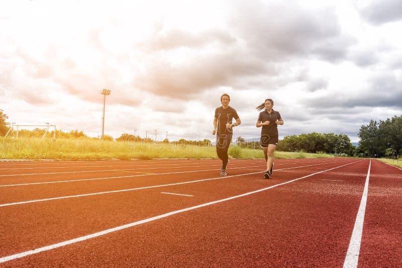 跑步在赛马跑道、体育和社交活动概念的两个赛跑者 免版税库存照片