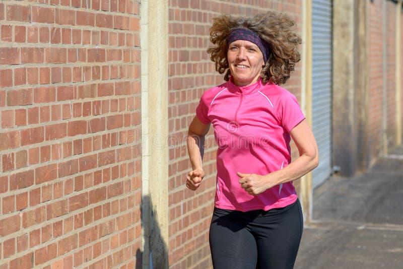 跑步在边路的镇的健康妇女 图库摄影