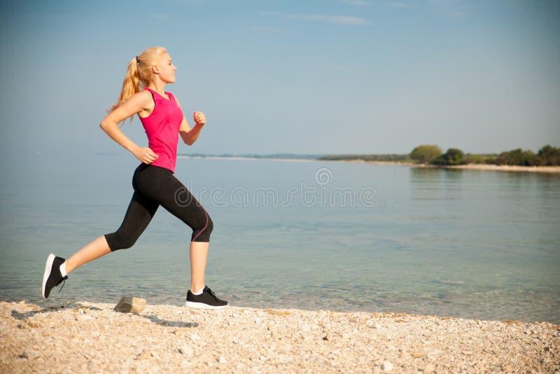 跑步在Th海滩-妇女runns临近初夏morni的海 图库摄影