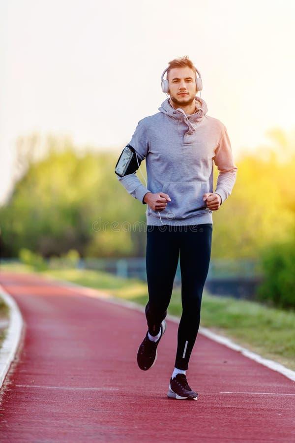跑步早晨的年轻人在赛马跑道 库存图片