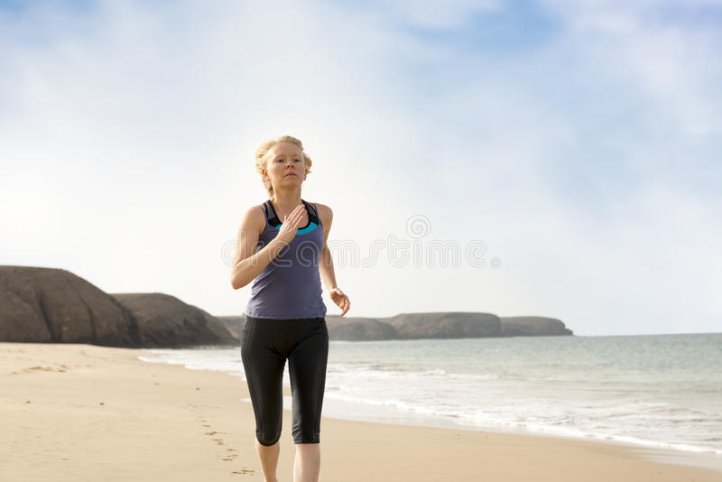 跑步由海岸的运动服的活跃夫人 库存图片