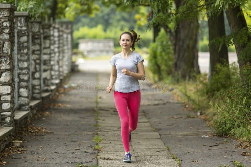 跑步的公园妇女年轻人 早晨凹凸部 健康生活方式 免版税库存照片